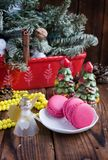 Pink macaroons with christmas decorations on wooden background Royalty Free Stock Image