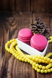 Pink macaroons with christmas decorations on wooden background Royalty Free Stock Photos