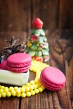 Pink macaroons with christmas decorations on wooden background Stock Photos