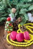 Pink macaroons with christmas decorations on wooden background Stock Photo