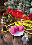 Pink macaroons with christmas decorations on woooden background Stock Photos