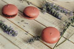 Pink macaroons and cup of coffee, on light wooden table royalty free stock photo