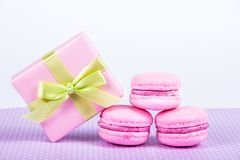 Pink macaroons and gift box. Almond macaroon cookies on white background. stock photos