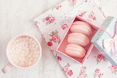 Pink macaroons in gift box with cup of coffee Stock Image