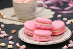 Pink macaroons are located on a plate on a dark background stock images
