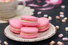 Pink macaroons are located on a plate on a dark background royalty free stock photos
