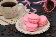 Pink macaroons are located on a plate on a dark background stock photos