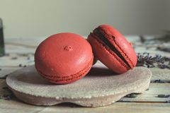 Pink macaroons and natural flowers on light wooden table royalty free stock photos