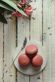 Pink macaroons and cup of coffee, on light wooden table stock photos