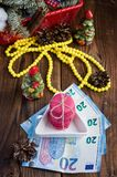 Pink macaroons and twenty euros with christmas decorations on woooden background Royalty Free Stock Images