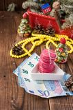 Pink macaroons and twenty euros with christmas decorations on woooden background Stock Photography