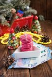 Pink macaroons and twenty euros with christmas decorations on woooden background Stock Photo