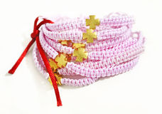 Pink macrame bracelets with gold cross Stock Photography