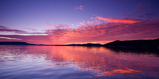 Pink Magenta Sunrise Seascape. Vivid pink magenta glowing sunrise over water with clear water reflections at Green Point on Bribane Water. Central Coast, New Royalty Free Stock Images