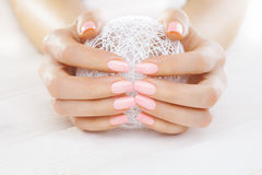 Pink manicure with a white ball of yarn. On the white wooden table stock photos