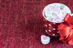 Pink marshmallow lie in a red cup in polka dots. Valentino`s day royalty free stock photography