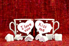 Pink marshmallow lie in a red cup in polka dots. Valentino`s day stock images