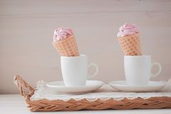Pink marshmallows or zephyr in white cups on the wooden background. Pink raspberry flavour marshmallows zephyr in white cups on the wooden background. Ice-cream Stock Images