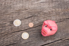 Pink marzipan pig with coins on wood. Pink marzipan pig with euro coins on wood Royalty Free Stock Photos