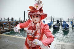 Pink mask. A beautiful pink mask celebrating the carnival in Venice with some moored gondolas on the background Royalty Free Stock Photography