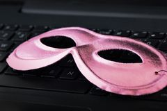 Pink mask on laptop keyboard - Concept of privacy, security and anonymity of women computer users. Pink mask on laptop keyboard. Concept of privacy, security and royalty free stock photography