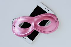 Pink mask on mobile phone - Concept of privacy, security and anonymity of mobile phone for women. Pink mask on mobile phone. Concept of privacy, security and stock photography