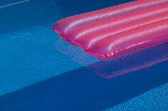 Pink mattress in pool. Blue water and pink plastic Royalty Free Stock Images