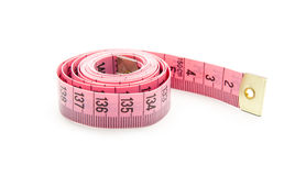 Measure. Pink measuring tape isolated on white background Royalty Free Stock Photography