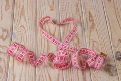 Pink measuring tape laid out in the form of a heart on a light background royalty free stock photography