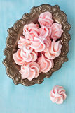 Pink meringue in antique old plate, on blue background,  top vie Stock Photo
