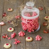 Pink meringue cookies in glass jar with heart on wooden table. Selective focus. Valentines Day concept. French dessert Meringue stock photo