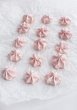 Pink meringues on baking paper Stock Photos