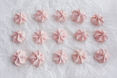 Pink meringues on baking paper Stock Images