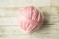 Pink merino wool ball. On wooden background royalty free stock images