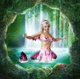 Pink Mermaid. A pink mermaid found a cave behind a waterfall Stock Images
