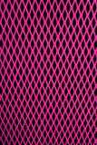 Pink Mesh. Pink metal grill of diamond shaped mesh, against a black background royalty free stock images