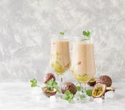 Pink milkshake with ice cubes and mint leaves and fruits of passion fruit on a marble table, selective focus Stock Images