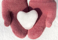 Pink mittens with snow heart. Hands with pink mittens holding snow heart Royalty Free Stock Photos