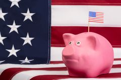 Pink money box for Money is worth on background the American flag. Pink money box for Money is worth on background Royalty Free Stock Images