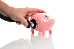 Pink money pigg with stethoscope Stock Photo