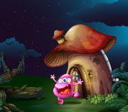 A pink monster near the mushroom house Royalty Free Stock Images