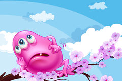 A pink monster resting at a branch of a tree Royalty Free Stock Image