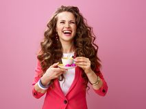 Cheerful young woman with cup of coffee and chocolate candies Royalty Free Stock Image