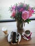 Pink mood for a coffee break. Delicious eclairs, coffee and flowers Stock Image