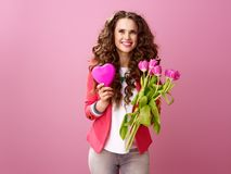 Woman with bouquet of tulips and heart shaped box of chocolate. Pink Mood. happy modern woman with long wavy brunette hair on pink background with a bouquet of Stock Images
