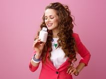 Woman isolated on pink background drinking farm organic yogurt Stock Photo