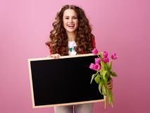 Happy young woman with bouquet of tulips showing blank board Stock Photography