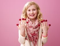 Happy child isolated on pink with raspberries on fingers. Pink mood. Portrait of happy stylish child with wavy blonde hair isolated on pink with raspberries on Royalty Free Stock Photo