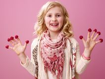 Happy girl on pink background showing raspberries on fingers. Pink mood. Portrait of happy stylish girl with wavy blonde hair on pink background showing Stock Images