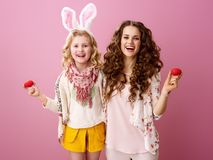 Mother and daughter on pink background with red Easter eggs. Pink Mood. Portrait of smiling stylish mother and daughter with wavy hair on pink background with Stock Image
